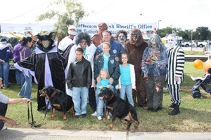 Group of people in costumes with some children and 2 rottweilers.