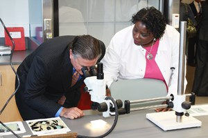 Man looking in a microscope with woman standing next to him
